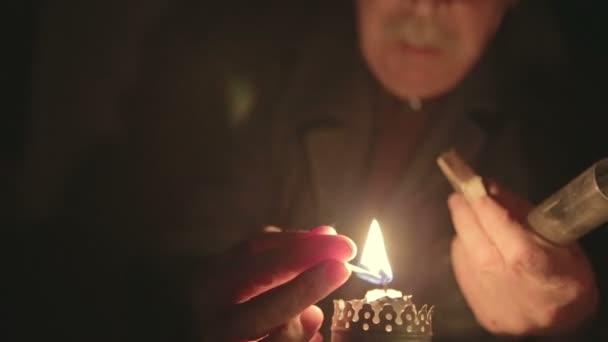 El abuelo enciende una vela en un cuarto oscuro — Vídeo de stock ...