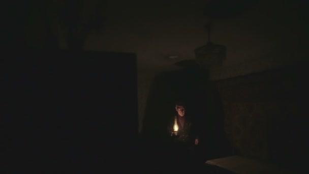 En un cuarto oscuro, una persona hace más luz usando la vieja lámpara de  gas.