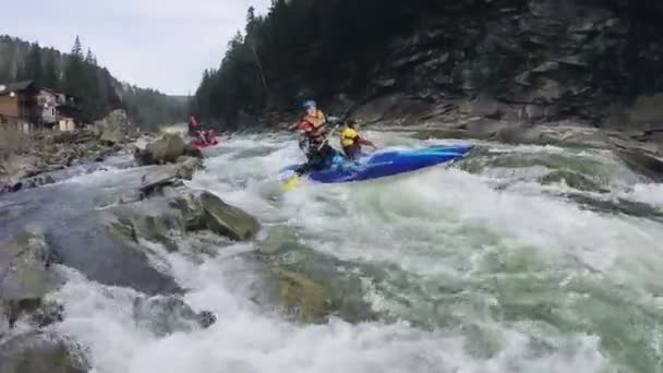 Rafting. Girl with a guy pass river rapids in a kayak. Slow motion