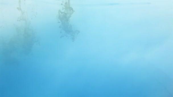 žlutý inkoust ve vodě na bílém pozadí