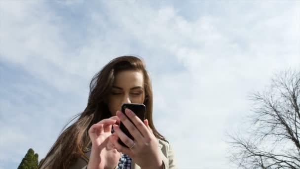 Frau hält Handy im park