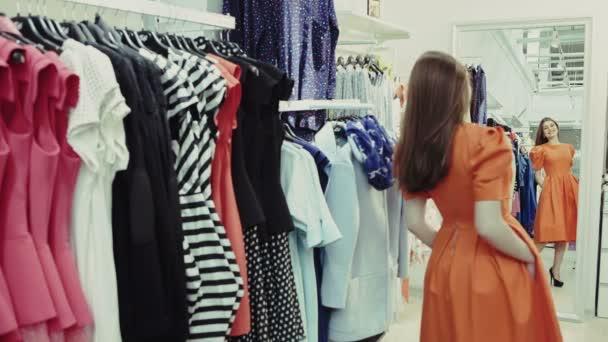 32a450150 Mulher de compras experimentando roupas vestido enquanto fazia compras em  loja de roupas durante a venda. bela jovem multicultural caucasiano  feminino ...