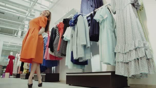 Žena, nakupování, při pohledu do zrcadla se šaty oblečení v obchod s oblečením. mladá krásná multikulturní žena se snaží na šaty přizpůsobit pokoj