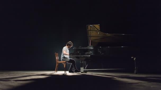 ein moderner klassischer Pianist spielt Klavier auf einer schwarzen Bühne