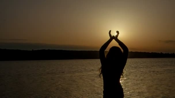 krásná mladá žena na pláži, sledování západu slunce, v rukou držel slunce