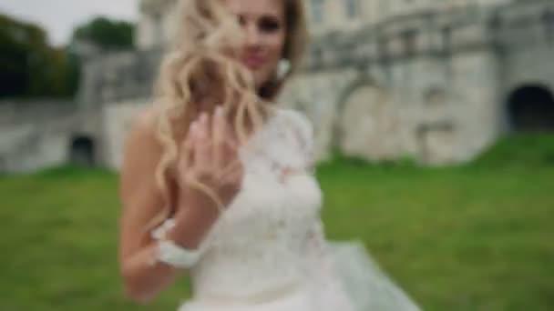 Dynamické video krásná blondýnka v bílých šatech s dlouhými vlasy. V létě krásné záběry od profesionálních modelů