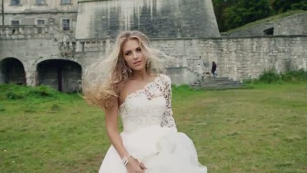 Ragazza felice in un abito da sposa di salto e movimento sullo sfondo di unantica mura del castello