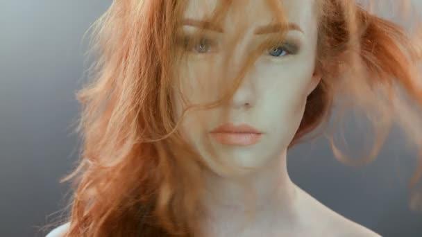 krásná dospívající dívka s červenými foukat vlasy a modré oči na šedé studio pozadí