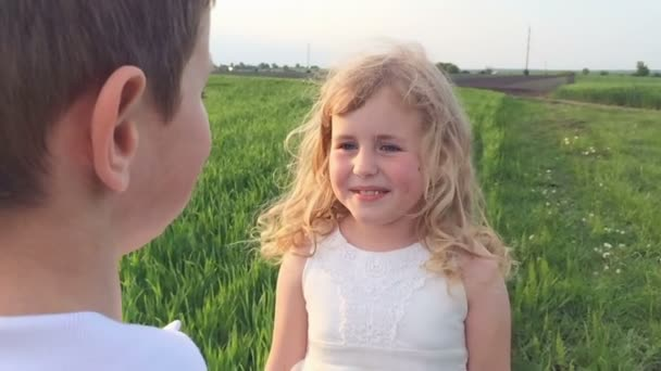 Young girl sincerely looking into the eyes of a young boy on a green spring field.  Slow motion.