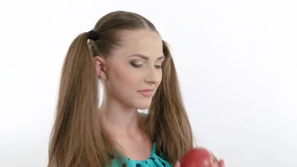 Attractive model eating an red apple on white background.  With audio. 4K raw video record.