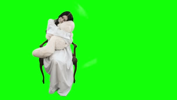 The girl in the image of a demon sitting on chair and embraces white toy bear. Shooting on Chroma key.