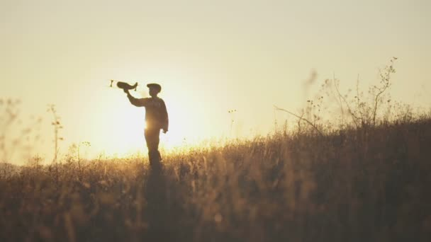 Šťastné dítě hraje s hračkou letadla proti pozadí oblohy letní oranžové slunce. Chlapec hrát letadlo na letní pole. Nejlepší koncept dětství