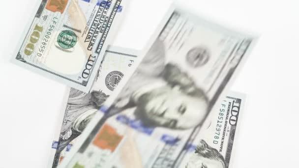 Klesající peníze, sto dolarové bankovky na bílém pozadí