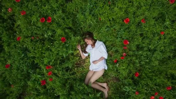 Pojezd jeřábu: Mladá žena leží v zelené trávě mezi máky