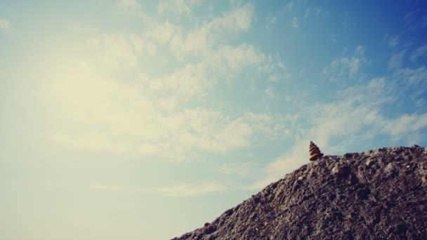 Krásné pozadí harmonie v přírodě. Pyramida z kamenů na písečném kopci