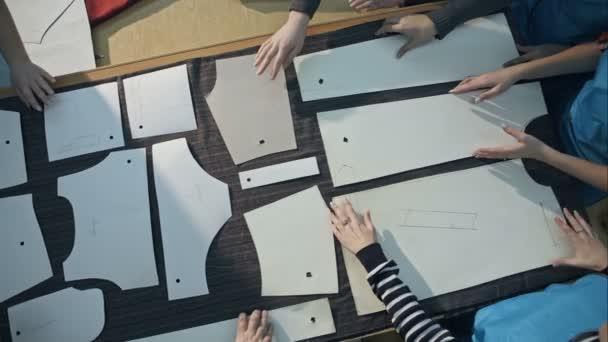 Das Team von jungen Designern Kleidungsstück Vorlagen Tuch ausgebreitet