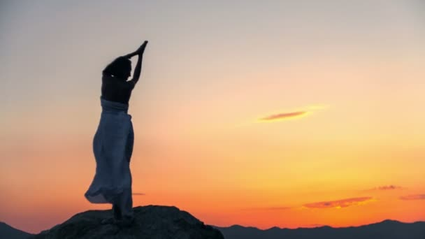 Siluetta di una ragazza in piedi sulle pietre nel mare al tramonto. Registrare video crudo