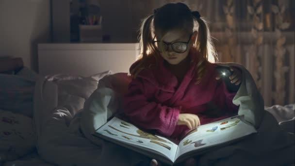 Malá dívka s brýlemi čtení knihy sedí v posteli pod peřinou. Velké potěšení. Surový video záznam