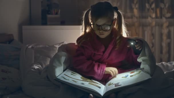 The little girl with glasses reading a book sitting in bed under the covers. Big pleasure. RAW video record.
