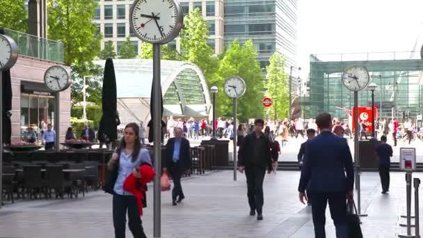London, Velká Británie - 03 července 2015: Dojíždějících spěchají do práce v Canary Wharf. Spousta lidí prochází známého náměstí s hodinami