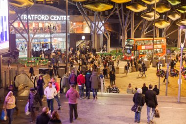 Stratford village square with shopping centre entrance and central bus stop and lots of people in Christmas rush