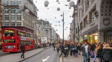 LONDON, UK - NOVEMBER 30, 2014: Regent street, Oxford circus with lots of pedestrians and cars, taxis on the road.