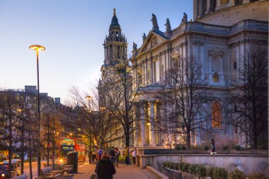 LONDON, UK - DECEMBER 19, 2014: City of London. St. Paul cathedral in dusk and red british double bus on the bus stop. People walking by the cathedral