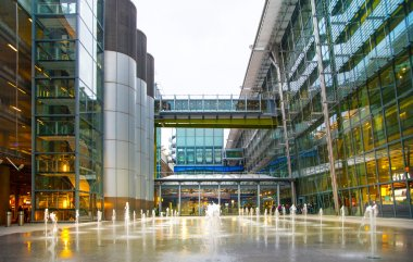 LONDON, UK -  MARCH 28, 2015: Heathrow airport Terminal 5 new square with fountains and wet reflected floor.