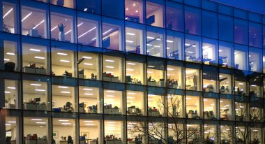 London, Office block with lots of lit up windows and late office workers inside. City of London business aria in dusk.