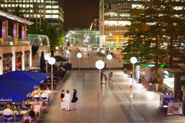 Canary Wharf square view in night lights with office workers chilling out after working day in local cafes and pubs. London