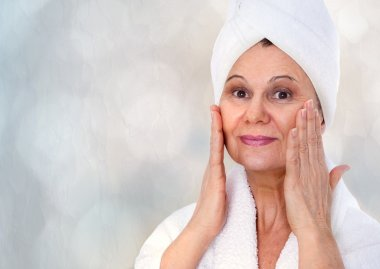 Spa concept. Aged good looking woman with white towel on her head