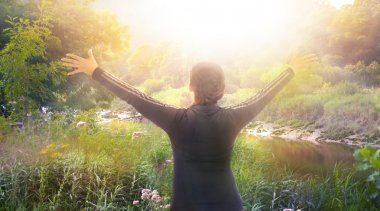 Sunrise, beautiful park and happy woman raising her hands up to the sun. Happy and healthy life concept
