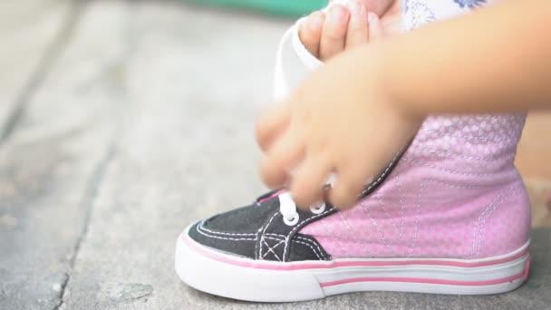 Hand von Kindern oder Mädchen lernen und versuchen, Bindung rosa Schnürsenkel oder Turnschuhe Seil und Schuhe zu Fuß für Spaziergänge und Mode auf der Straße mit unabhängigen und kostenlos auf langsam