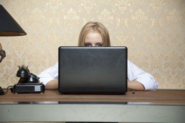 Business woman hiding behind a laptop