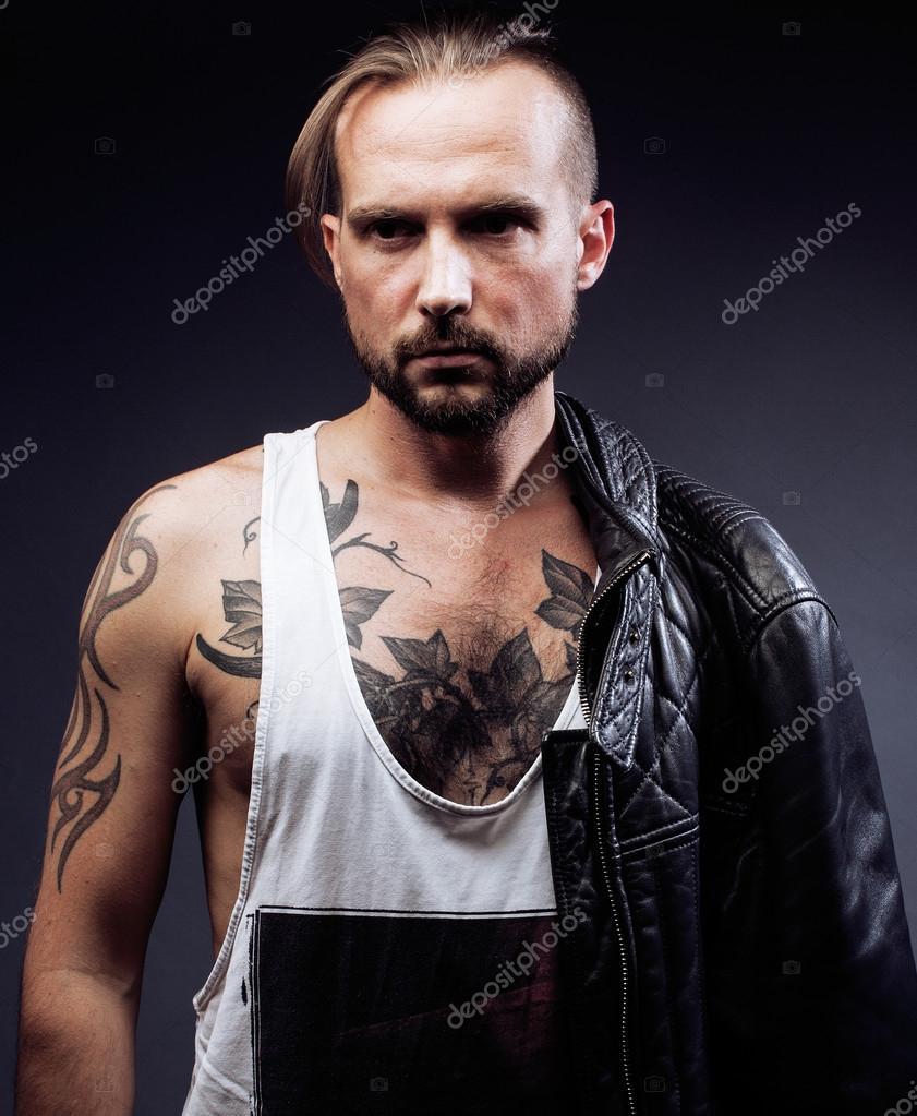 Un hombre con el tatuaje en sus brazos. Silueta de cuerpo musculoso. chico  caucásico brutal hipster con corte de pelo moderno 9584b50fe03