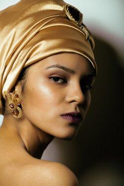 beauty african woman in shawl on head, very elegant look with gold jewelry close up