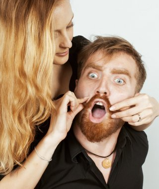 young hipster couple fooling around on white background close up, both ginger