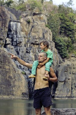 Father and son making a trip to waterfall together, happy family on vacations, nature place pongour