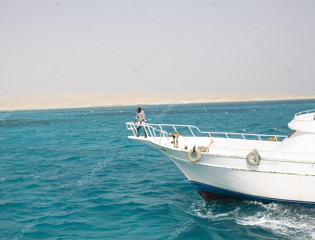 white boat with african black skin fishman on board in red sea egypt