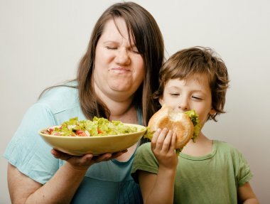 mature woman holding salad and little cute boy with hamburger teasing close up