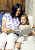 portrait of mother and daughter staying at home reading book smiling