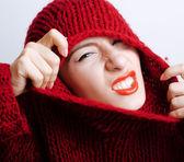mladá žena skutečné červený svetr a šátek celé její tvář, usmívající se doma, zimní pozitivní