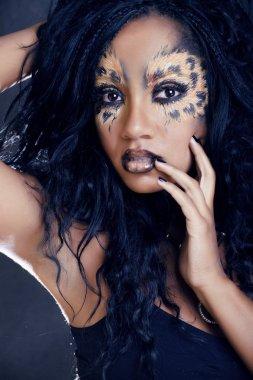 beauty afro girl with cat make up, creative leopard print closeup halloween