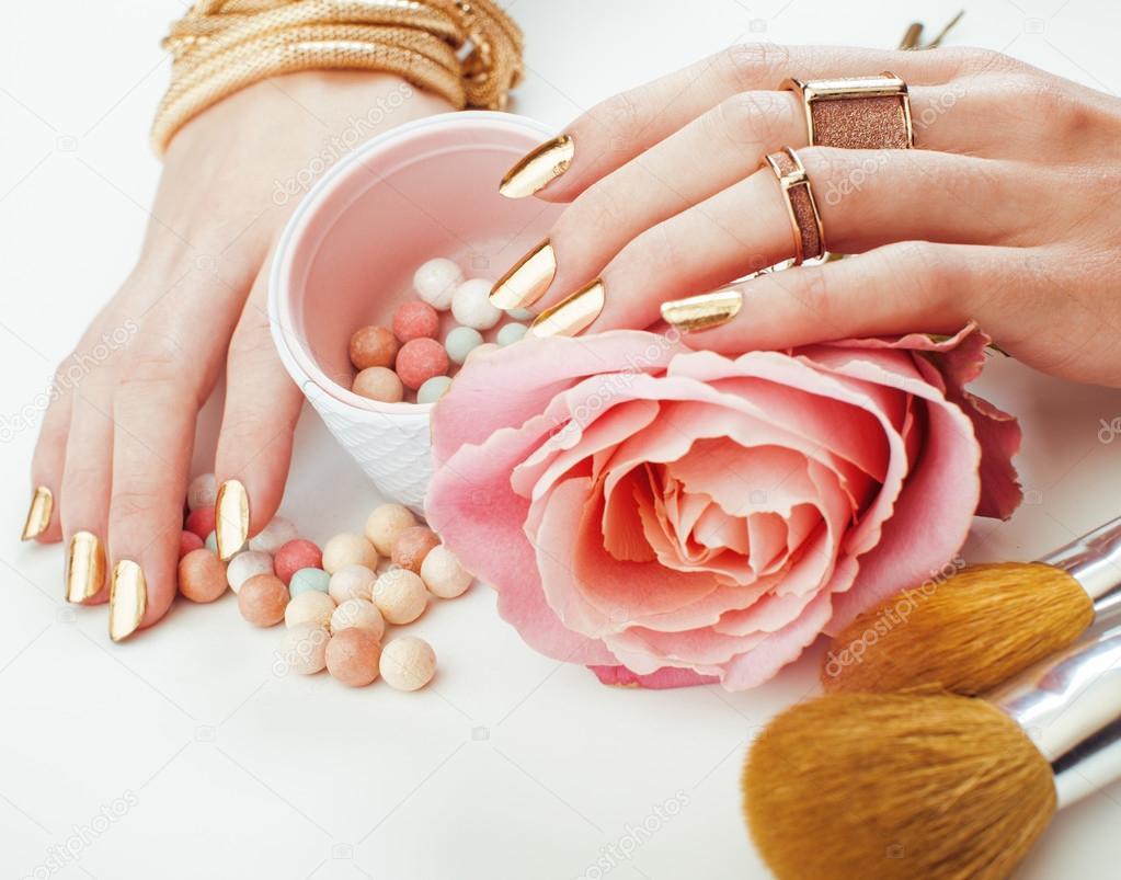 f67cd1b365da žena ruce zlatý manikúru a mnoho kruhy těsně drží štětce