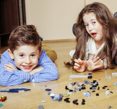 funny cute children playing lego at home, boys and girl smiling, first education role close up