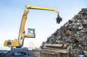 Velké pásové rypadlo pracující ocelové hromadu na kovové koše