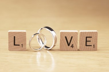 The Word Love with Wedding Rings and Scrabble Pieces