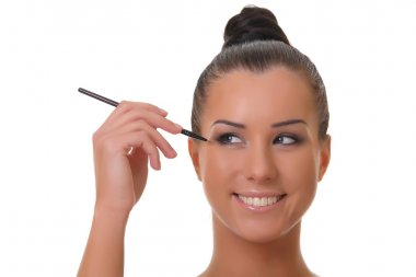 Beautiful young woman holds the make-up brushes