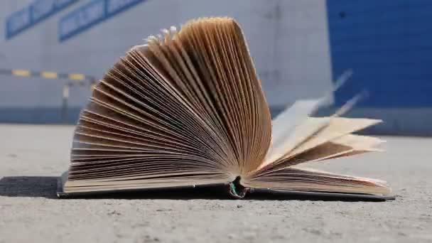 Fordítsd el a könyv lapjait a szélben. A könyv az aszfalton fekszik..