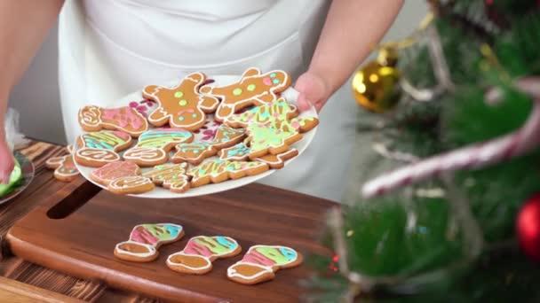 A nő karácsonyi mézeskalácsot süt színes cukormázzal a tányéron